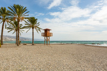 Empty Sandy Beach In Winter With Palm Tree And Life Guard Stand In Winter