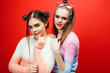 Leinwanddruck Bild - two best friends teenage girls together having fun, posing emotional on red background, lifestyle people concept