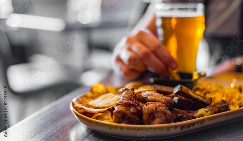 In de dag Kip man hand with glass of cold beer and plate with snacks on wooden table background on bar or pub