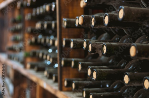dusty wine bottles on a wooden shelf in a wine cellar Fototapet