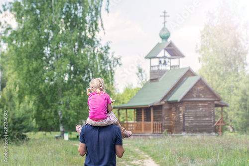 Fényképezés  Man carries a little girl on his shoulders to an old wooden church