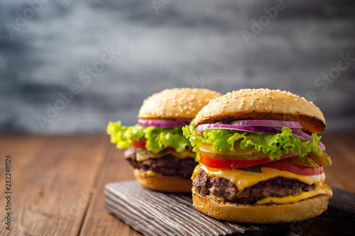 Carta da parati  Two homemade tasty burgers on wood table. Selective focus.