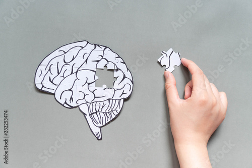 Female hand trying to connect a missing jigsaw puzzle of human brain on gray background Wallpaper Mural