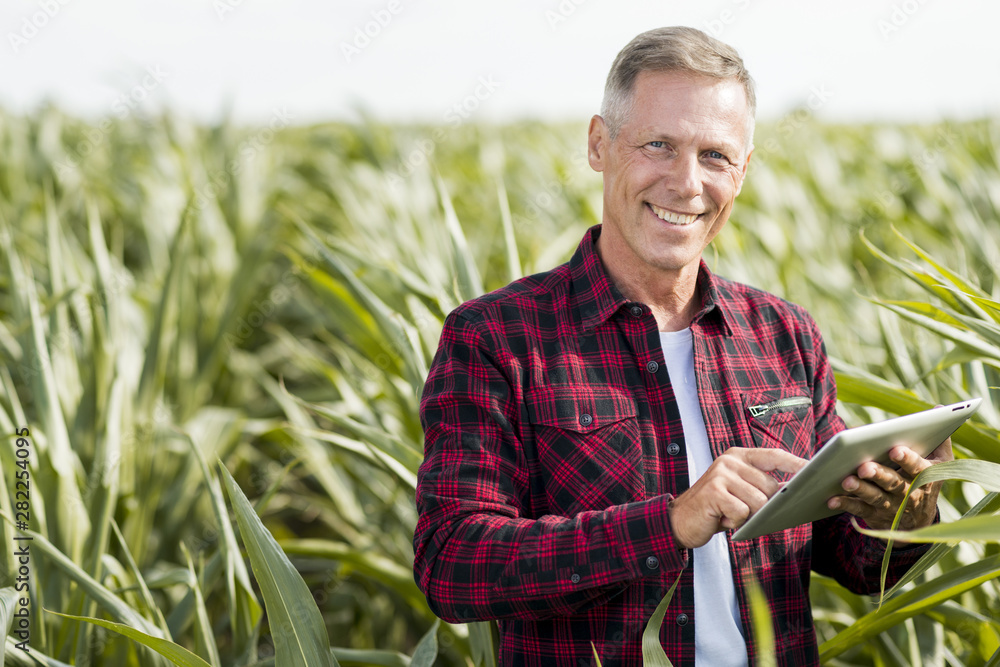 Fototapety, obrazy: Man looking at camera with a tablet