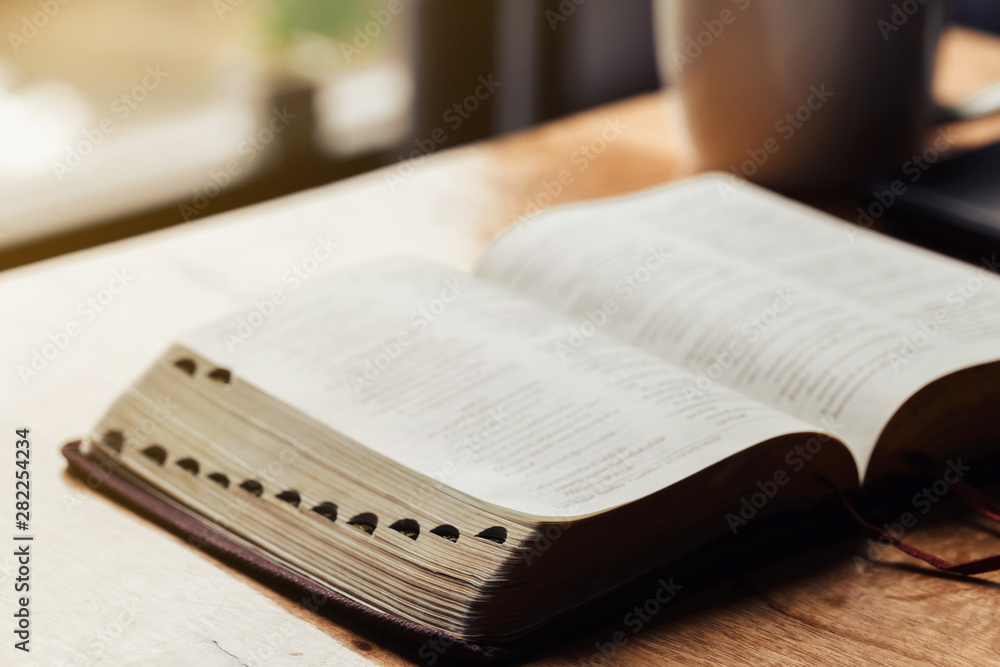 Fototapety, obrazy: Open bible with a cup of coffee for morning devotion on wooden table