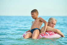 Grandfather And Grandson Swim In The Sea In An Inflatable Circle