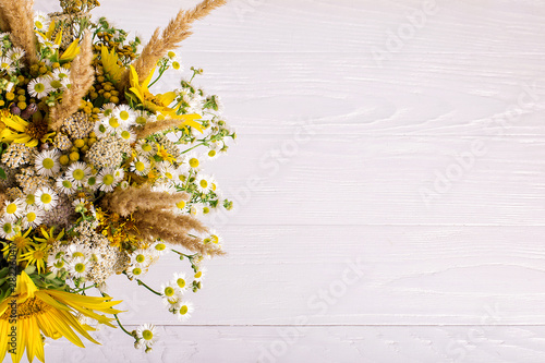 Obraz Wildflowers in a handmade vase, on a white background on the table. Copy space. - fototapety do salonu