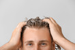 canvas print picture - Handsome young man washing hair against grey background