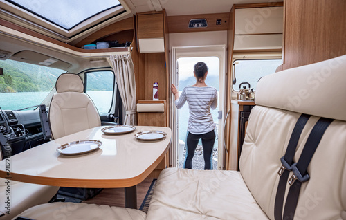 Woman in the interior of a camper RV motorhome with a cup of coffee looking at nature Fototapete
