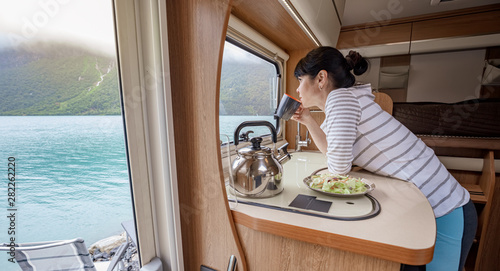 Tableau sur Toile Woman in the interior of a camper RV motorhome with a cup of coffee looking at nature