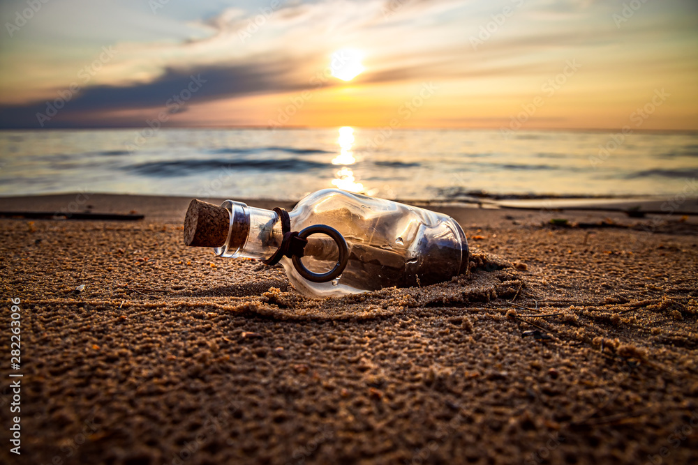 Fototapety, obrazy: Message in the bottle against the Sun setting down