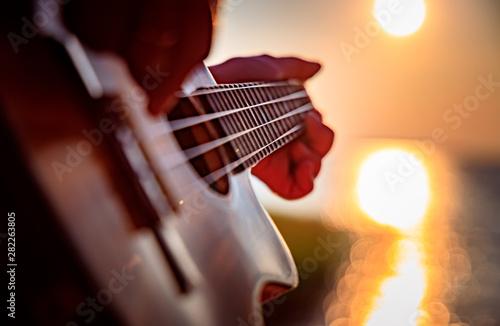 Woman at sunset playing the ukulele - 282263805