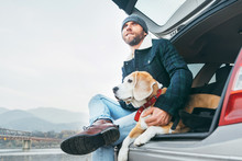 Man With Beagle Dog Siting Together In Car Trunk
