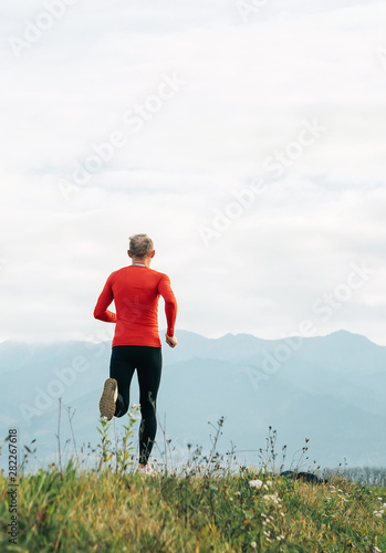 Fotografie, Obraz  Man dressed in red long sleeve shirt runs by the road with mountain background vertical shoot