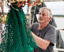 Weathered Commercial Fisherman Mending A Net On A Boat Off The Coast Of South Carolina.