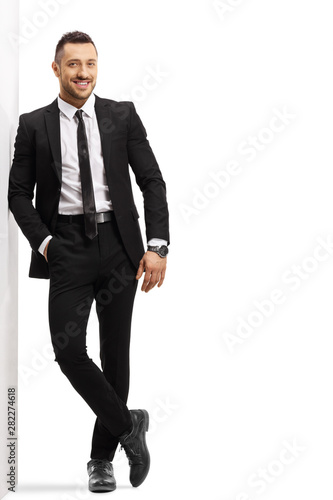 Cuadros en Lienzo  Young cheerful man in a black suit leaning on a wall