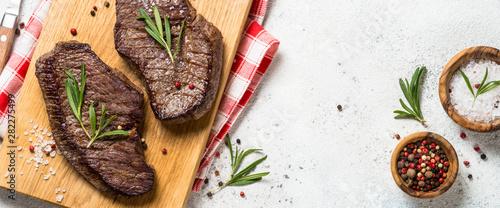 Obraz na plátně  Grilled beef steak on wooden cutting board.