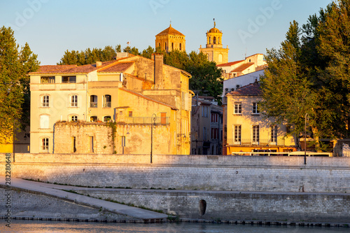 Arles. City embankment and facades of old houses at sunset. Canvas Print
