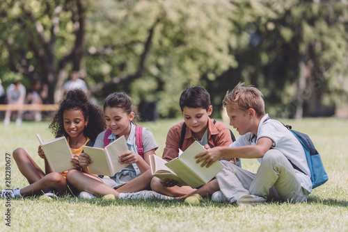 four adorable multicultural schoolkids sitting on lawn and reading books Canvas-taulu