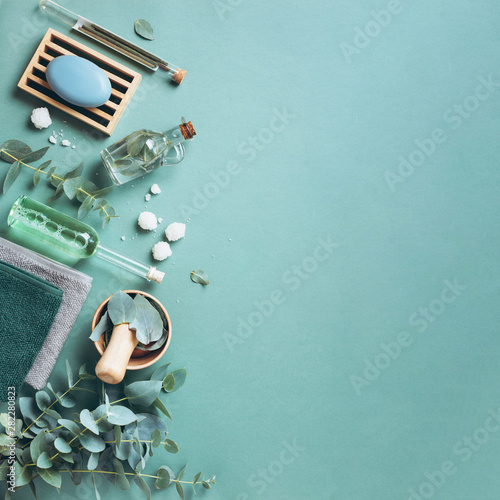 Fototapeta Soap, eucalyptus, towels, massage brush, salt, aroma oil and other spa objects on green background. Top view. Skin care, body treatment concept. Banner. obraz na płótnie