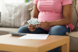 savings, finances and people concept - close up of pregnant african american woman with papers and calculator counting money at home