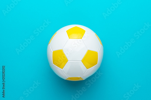 Top view photo of white and yellow soccer ball over turquoise blue background with copy space Canvas-taulu