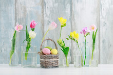 Colorful Flowers In Glass Bottles And Easter Eggs In Wicker Basket On The Table