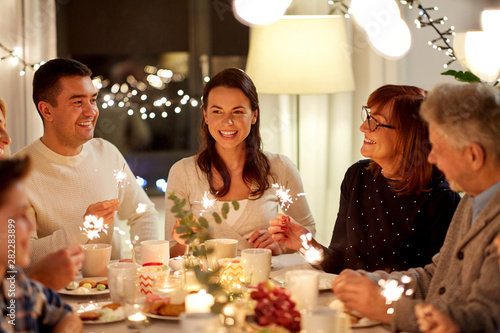 Fototapety, obrazy: celebration, holidays and people concept - happy family with sparklers having tea party at home