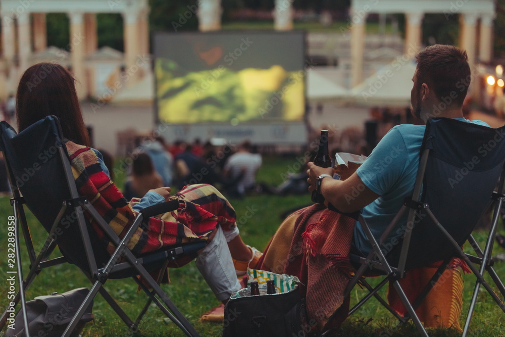 Fototapety, obrazy: couple sitting in camp-chairs in city park looking movie outdoors at open air cinema