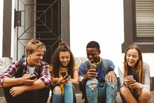 Friends Sitting Outdoors Holding Cell Phones