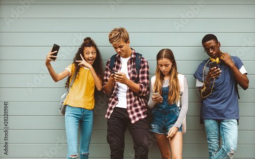 Teenage friends looking at their mobile phones - 282289841