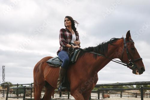 Fototapeta Woman riding her horse in corral obraz