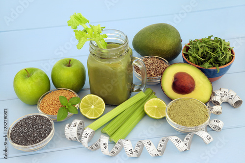 fototapeta na lodówkę Health food diet drink with fresh fruit, vegetables, matcha powder, flax, chia and hemp seed on blue wood background with tape measure. High in omega 3, antioxidants, vitamins and dietary fibre.