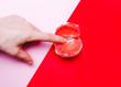 Leinwandbild Motiv fingers in grapefruit, vagina symbol on a red background