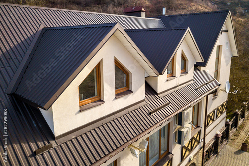 Canvas Print Close-up aerial view of building attic rooms exterior on metal shingle roof, stucco walls and plastic windows