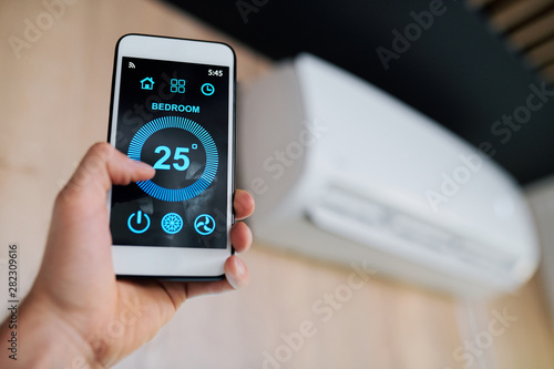 Fotografía  Optimal temperature of air in the room shown on display of smartphone