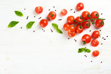 Bunch Of Juicy Organic Red Cherry Tomatoes Arranged With Green Basil Leaves On Isolated White Background. Polished Vegetables. Clean Eating Concept. Vegetarian Diet. Copy Space, Flat Lay, Top View.