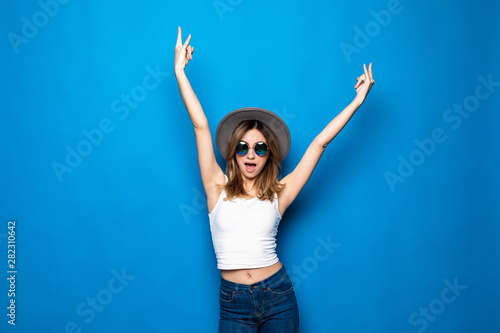 Leinwand Poster  Cheerful healthy girl raising her hands up with enjoyment isolated on blue backg