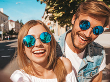 Smiling Beautiful Girl And Her Handsome Boyfriend In Casual Summer Clothes.Happy Family Taking Selfie Self Portrait Of Themselves On Smartphone Camera In Sunglasses.Having Fun On The Street Background