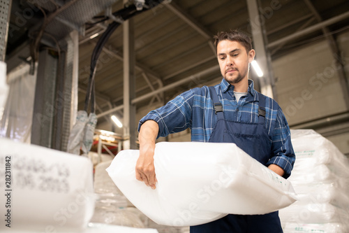 Obraz Young man in workwear carrying heavy white sack with polymer granules - fototapety do salonu