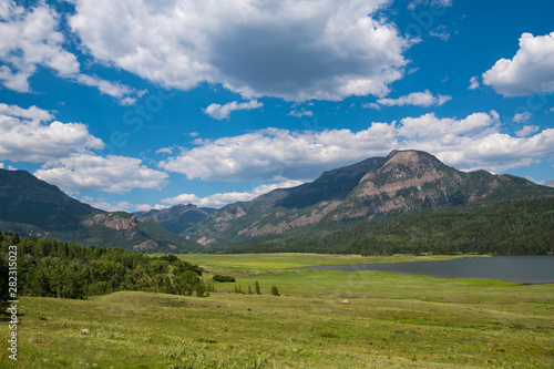 Fototapeta Lush green grasslands and lake below the Rocky Mountains and a blue sky with white clouds near Pagosa Springs, Colorado obraz na płótnie