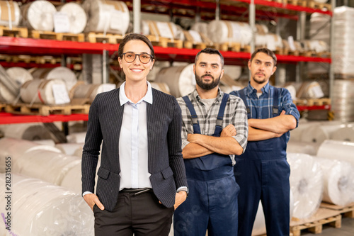 Poster Ouest sauvage Happy young elegant female leader of engineering team and two men in workwear