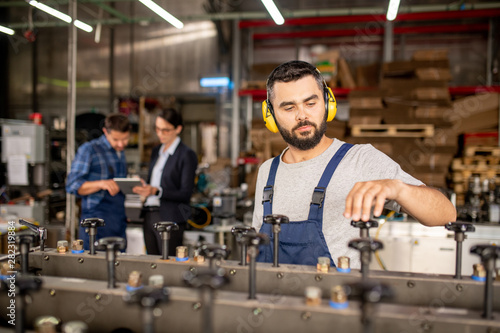 Young bearded mechanic in protective headphones repairing industrial machine