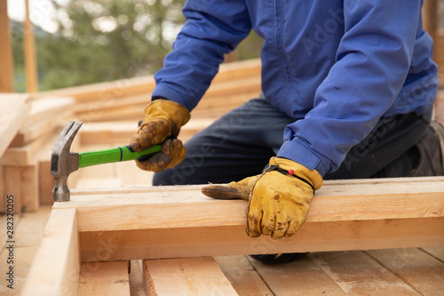 Fotografiet Male builder in yellow gloves hammer nail into wooden structure