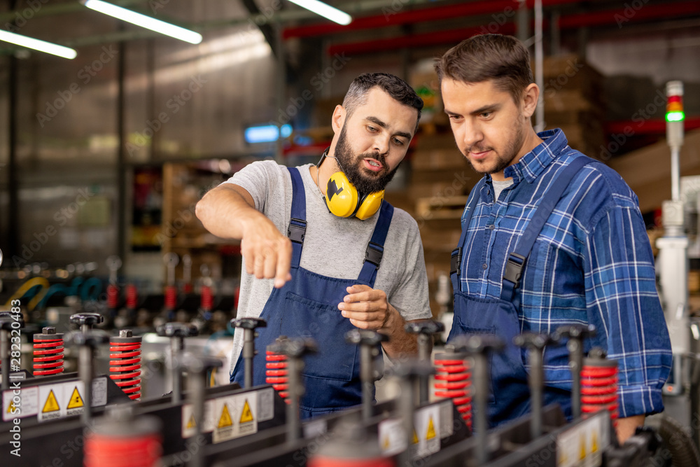 Fototapety, obrazy: Young trainee looking at industrial equipment while listening to manager