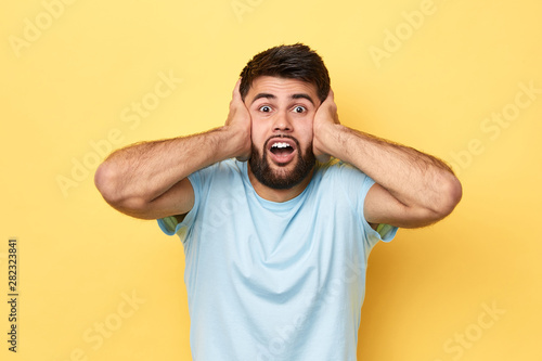 oh, my God, man with bugged eyes doesn't want to listen to the music, close up portrait, isolated yellow background - 282323841