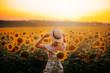 Leinwanddruck Bild - bright delightful atmospheric photo, summer field of sunflowers, large yellow flowers and girl in light beige dress and straw boater, lady against hot sun, model from back, no face, free country life
