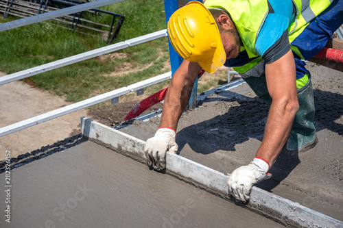 Worker with yellow helmet straighten and smoothing fresh concrete on a construction site