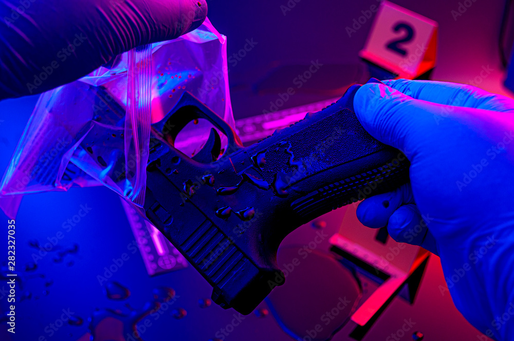 Fototapeta Forensic science, murder weapon and criminal investigation concept theme with detective wearing latex gloves bagging gun to send to lab in a dark crime scene illuminated by red and blue cop car lights