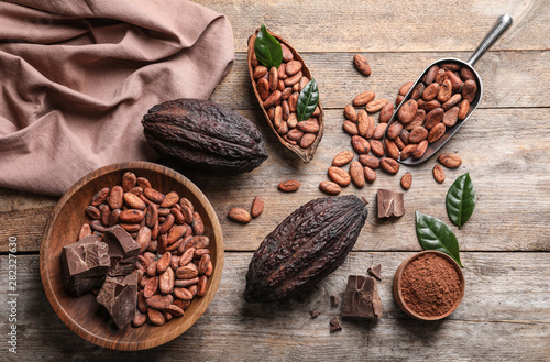 Canvas Prints Countryside Flat lay composition with cocoa beans, chocolate pieces and pods on wooden table